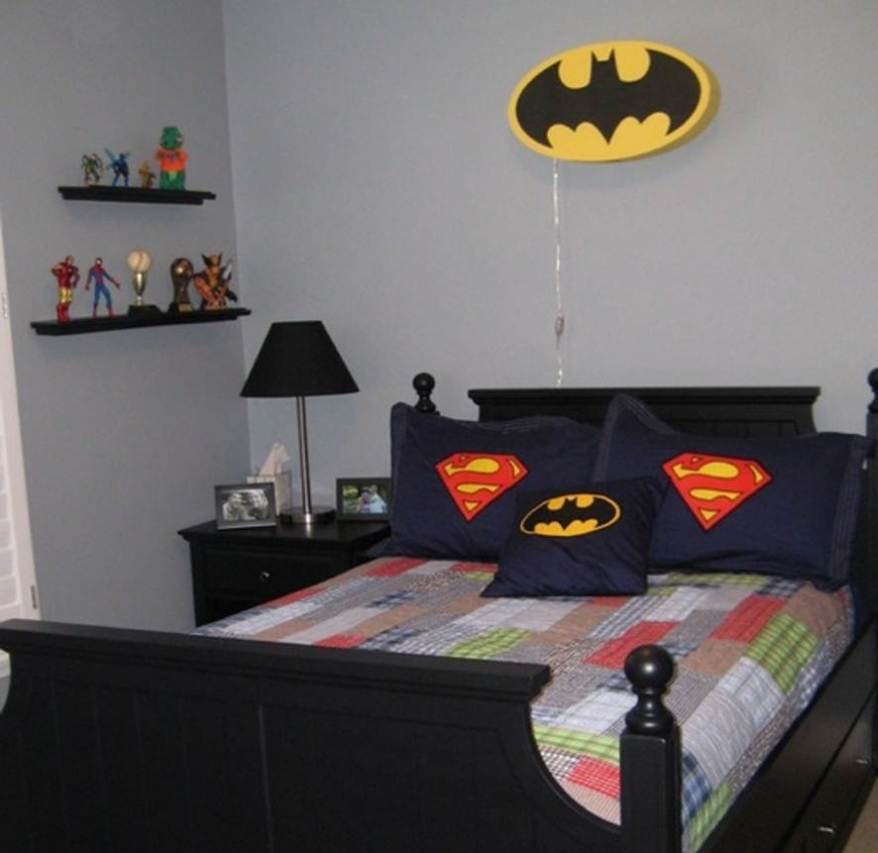 Simple-superhero-bedroom-with-Batman's-and-Superman's-symbols-applied-on-pillow-covers-black-shelves-for-organizing-the-miniature-of-superhero-black-paint-bedside-table-with-black-table-lamp.jpg